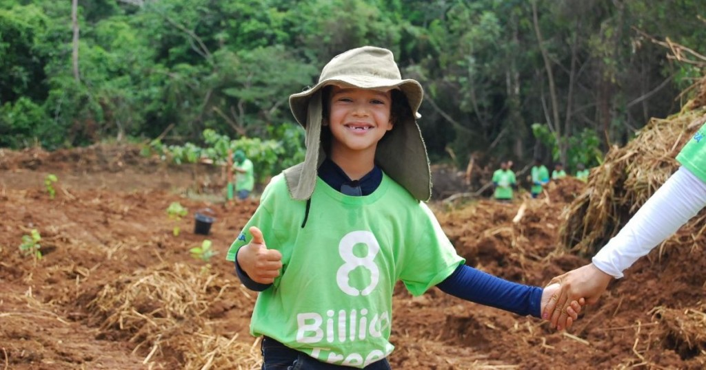 8 Billion Trees brand image of a kid smiling giving a thumbs up while wearing a green 8 Billion Trees t-shirt and holding hands with his mother at a tree planting site in the Amazon Basin