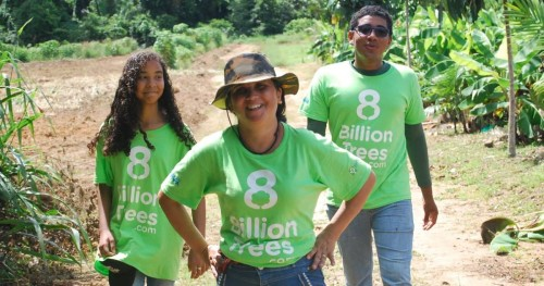 Three 8 Billion Trees team members smiling and walking alongside a tree planting site in a remote tree location deep in the Amazon Rainforest(Tocantins Region) after completing the mission of planting native species saplings during a forestry project aimed at reducing greenhouse gases