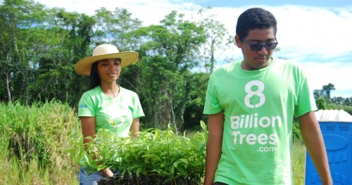 Two 8 Billion Trees team members smiling and carrying over a dozen native species saplings to tree planting site in a remote tree location deep in the Amazon Rainforest(Tocantins Region) on EarthDay during mission to make ecological impact