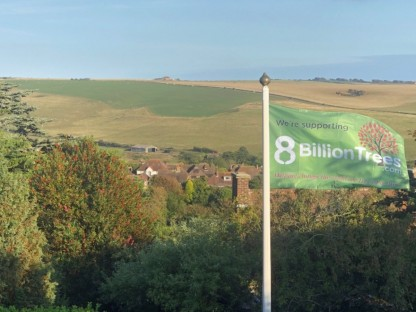 An 8 Billion Trees flag waving in the wind with trees and grassy hills in the background