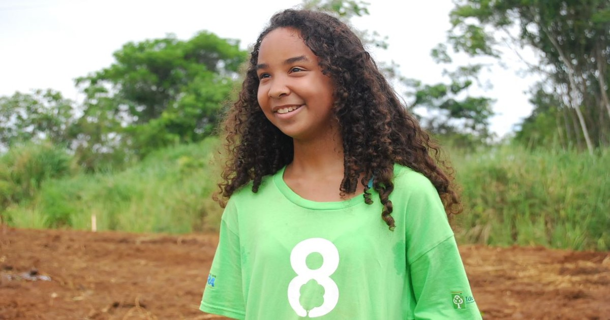 8 Billion Trees Brand Image of young girl smiling with an 8 Billion Trees t-shirt at a tree planting site in the State of Tocantins, a remote area in the Amazon Basin, excited to help plant trees