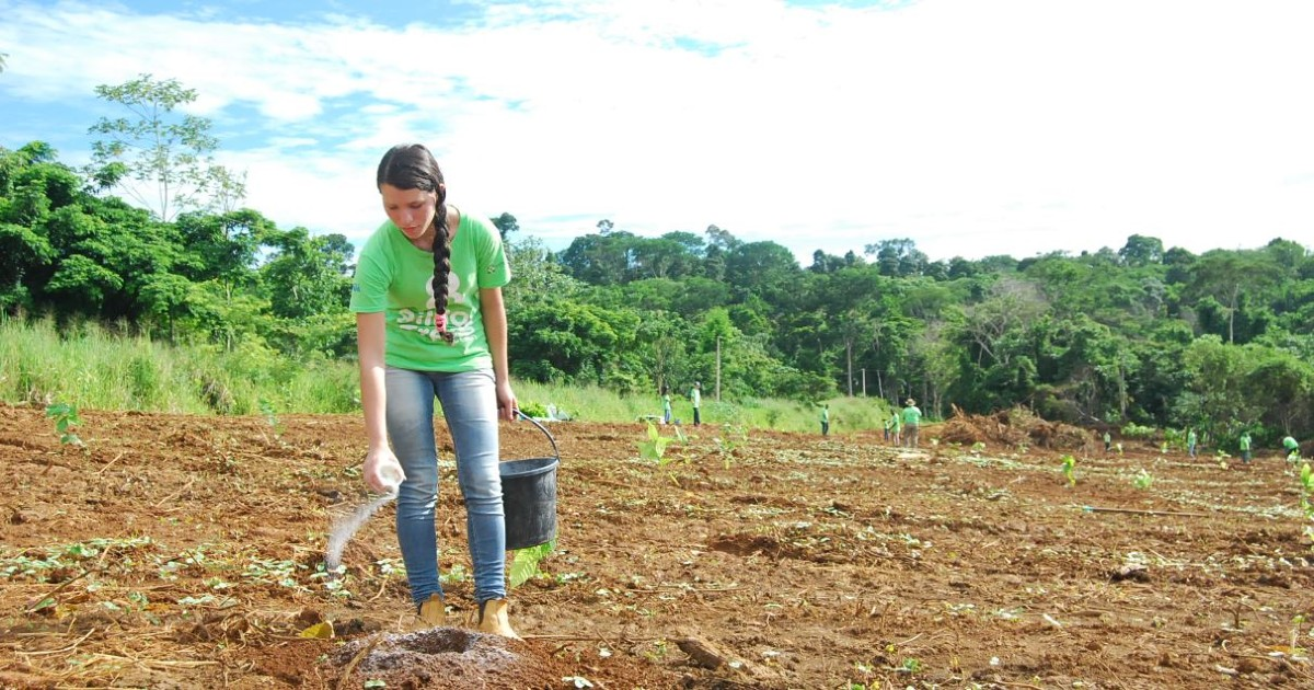 A woman leaning over and watering a hole at a reforestation site in Tocantins Brazil