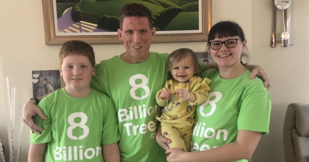 Alastair Hazell holding his family and smiling in 8 Billion Trees t-shirts