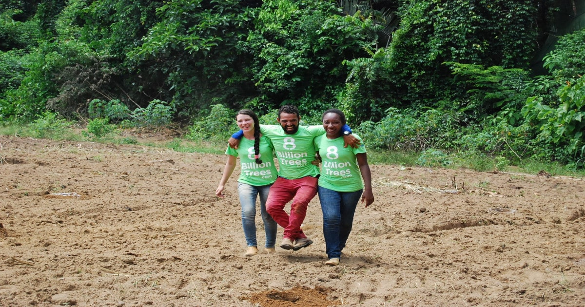 Three people in 8 Billion Trees t-shirts with their arms around one another while walking through a planting site.