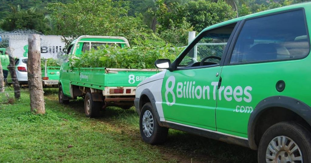 A line of cars driving through a gate with 8 Billion Tree logo on them and a forest in the background.
