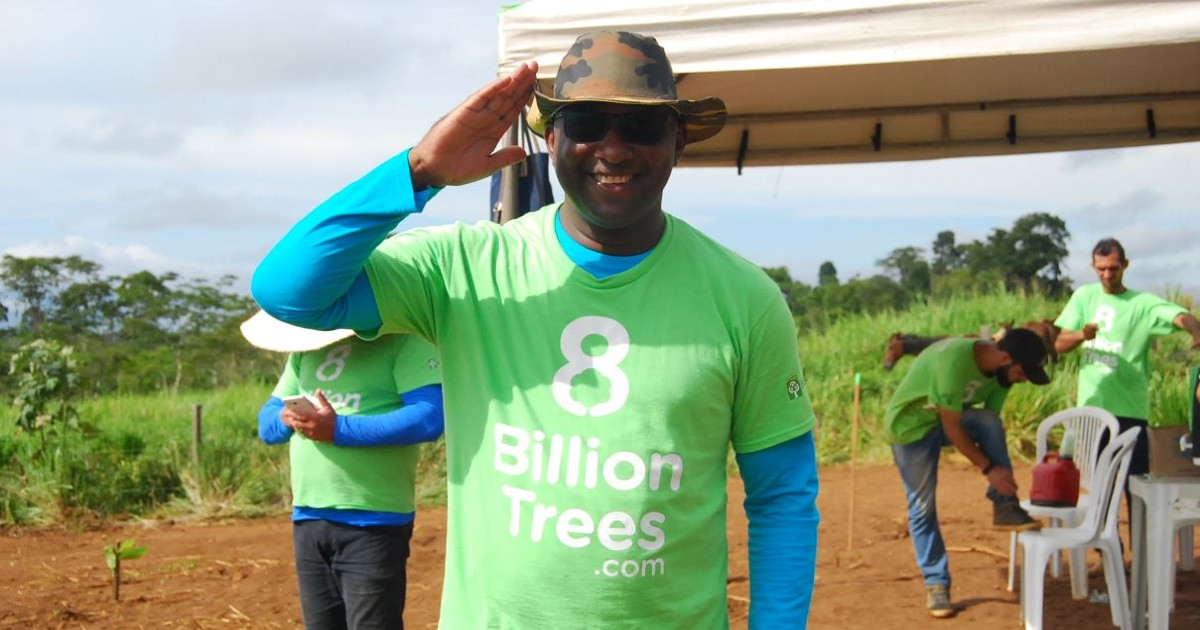 8 Billion Trees Team Member in a green 8 Billion Trees t-shirt salutes the camera with the rest of the team in the background under a tent at a tree planting site in the Brazlian State of Tocantins, Amazon Basin area targeted for tree planting and other carbon offsets