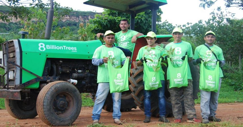 Five men in the Amazon Rainforest holding CO2 sequestering saplings in front of a tractor with 8 Billion Trees shirts on