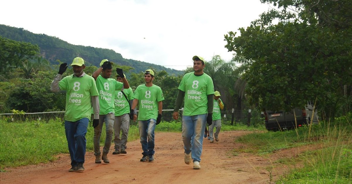 Six men in 8 Billion Trees (a provider of carbon offsets) t-shirts saving gas (fossil fuels) by walking on a dirt path in the Amazon Rainforest