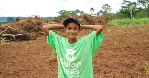Young kid standing in the middle of an open field wearing an 8 Billion Trees brand green t-shirt raises his hands after a tree planting education session aimed at teaching kids the importance of calculating emissions in the central Amazonian State of Brazil