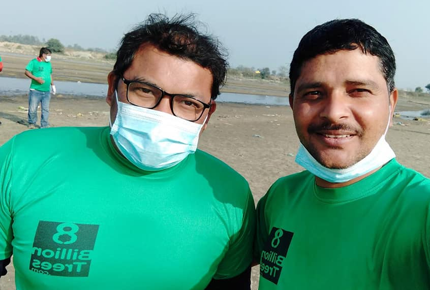 8 Billion Trees team members wearing world map t-shirt at beach during trash cleanup project day