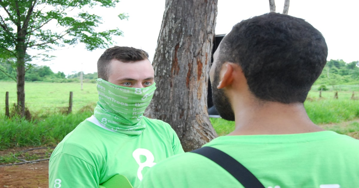 8 Billion Trees founder Jon Chambers discussing forestry matters with a colleague while wearing a eco-friendly branded shirt and bandana.