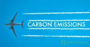 """A plane releasing smoke that says """"carbon emissions"""" in the blue sky"""