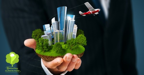 A business man in a suite holding a segment of earth with buildings on it and a plane flying away.