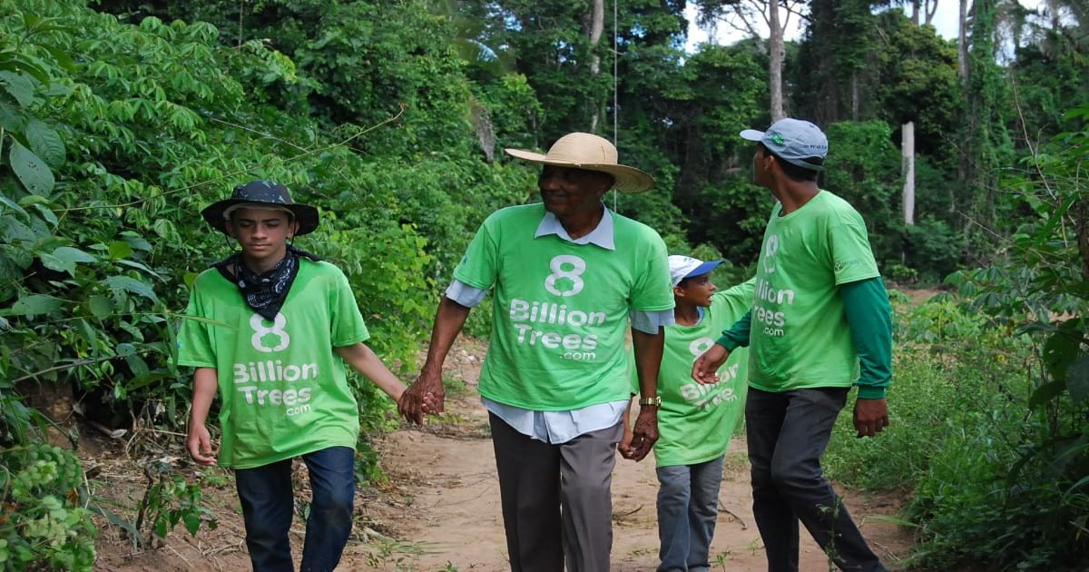 Image of a family of four walks down dirt trail wearing hats and 8 Billion Trees brand t-shirts while two hold hands and the other two members look around at the lush green environment deep in the heart of central Brazil near the Amazon Basin