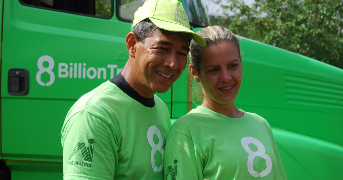 Image of two 8 Billion Trees team members(man and women) smiling standing next to each other wearing 8 Billion Trees brand green t-shirts in front of a green hauling truck in remote location of Amazon Basin
