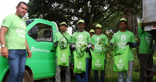 Five 8 Billion Trees team members holding sapling bags that are ready to be planted in front of a green truck with an 8 Billion Trees Logo on the door