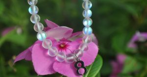 Sustainable jewelry with background of a pink flower