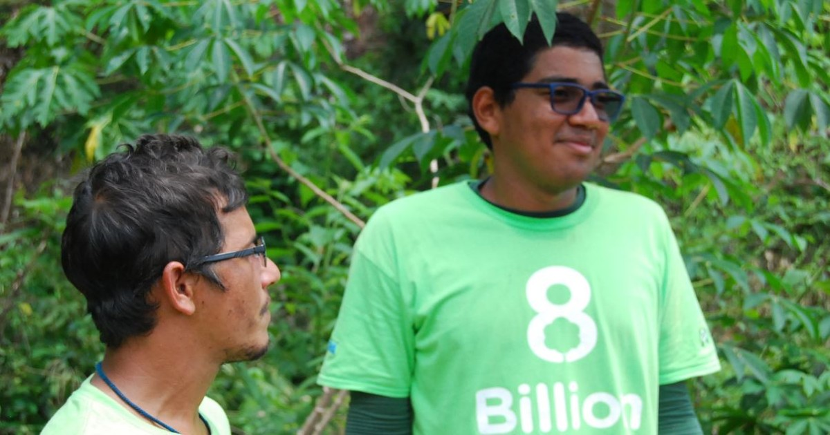 Image of Two 8 Billion Trees Team members standing under a tree for shade wearing green 8 Billion Trees brand t-shirts as looking off into the forest in the Amazon State of Tocantins