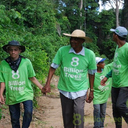 Family in Brazil walking to plant trees nearby.