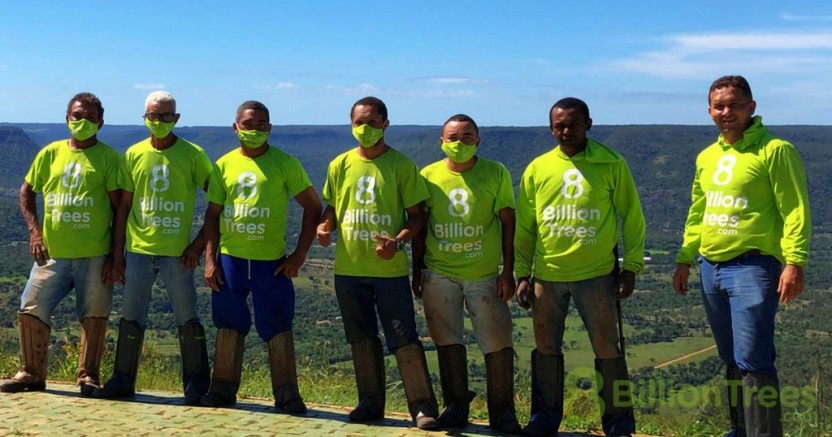 Team members in 8 Billion Trees shirts and work boots posing at a planting site in Brazil, with an 8 Billion Trees watermark